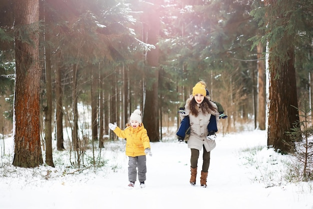 Happy family playing and laughing in winter outdoors in the snow. city park winter day.