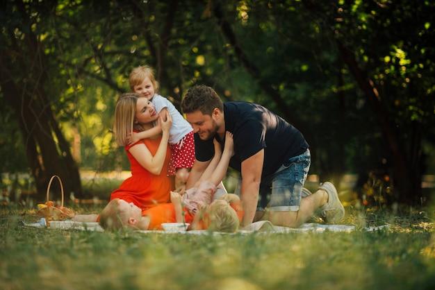 幸せな家族のピクニック毛布で遊んで