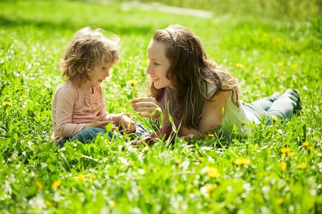 春の公園で緑のフラスで遊んで幸せな家族
