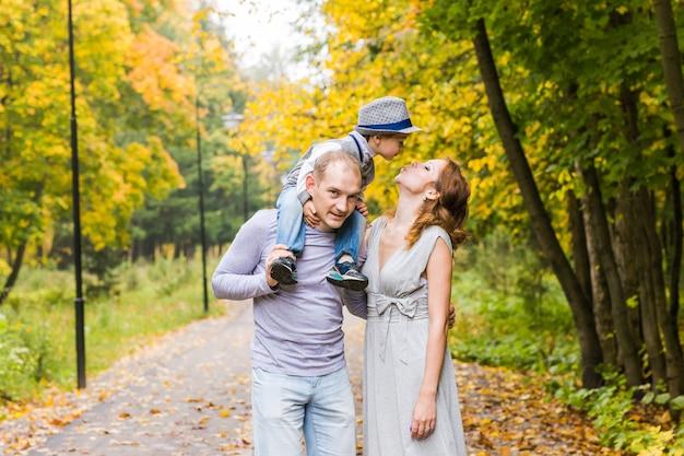 秋の公園でおんぶをしている幸せな家族。