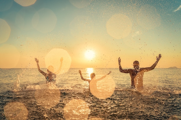 Happy family playing in the sea people having fun outdoor summer vacation and healthy lifestyle concept