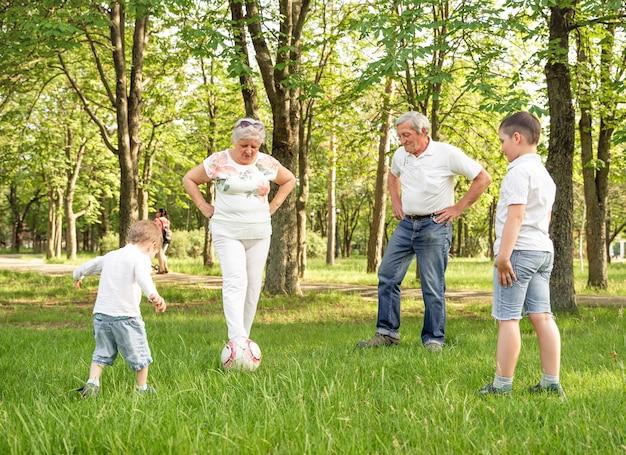 夏の牧草地でサッカーをしている幸せな家族。アクティブな家族