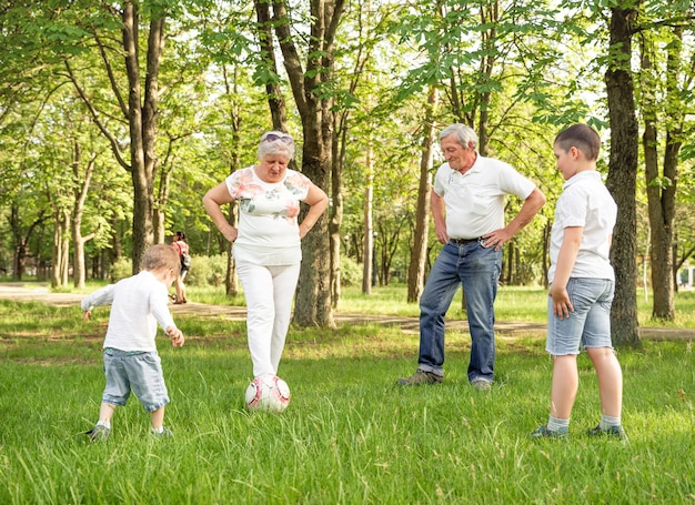 Happy family playing soccer on summer meadow. active family
