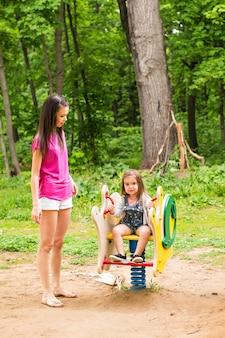 屋外の公園で一緒に遊んで幸せな家族。