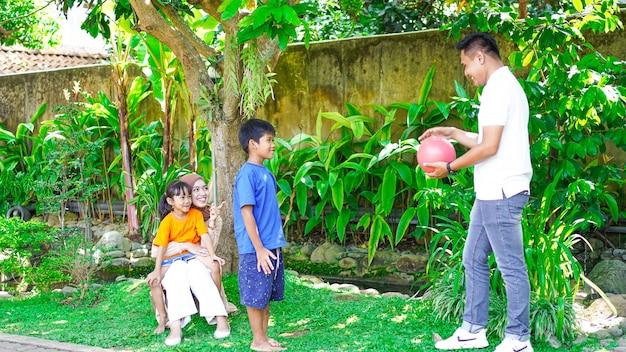 庭で一緒に遊ぶ幸せな家族