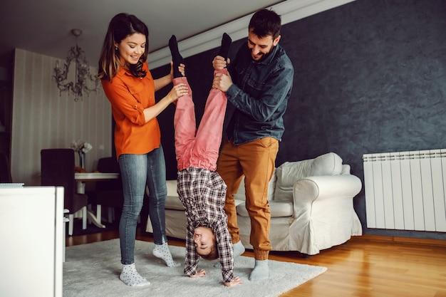 一緒に遊んで幸せな家族。母と父は娘に倒立の仕方を教えています。