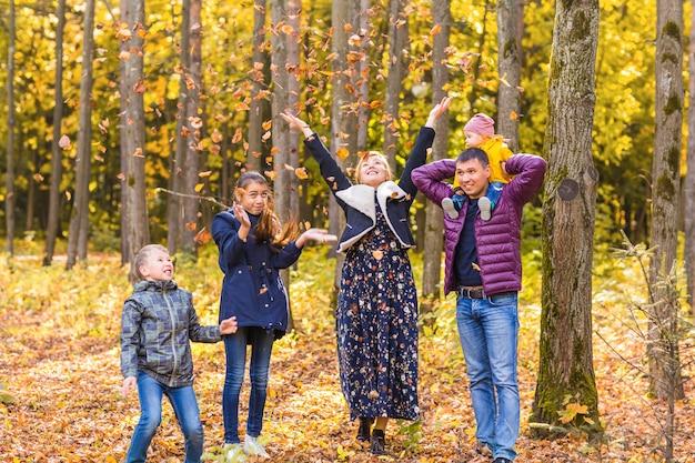 公園で紅葉で遊ぶ幸せな家族