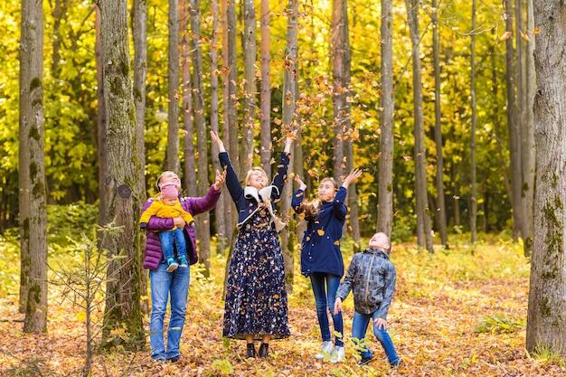 公園で紅葉で遊ぶ幸せな家族 Premium写真