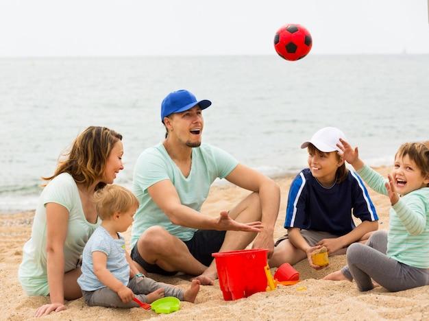 Счастливая семья, играя с мячом на песчаном пляже
