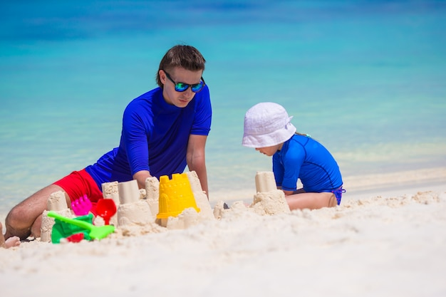 Happy family playing with beach toys on summer vacation