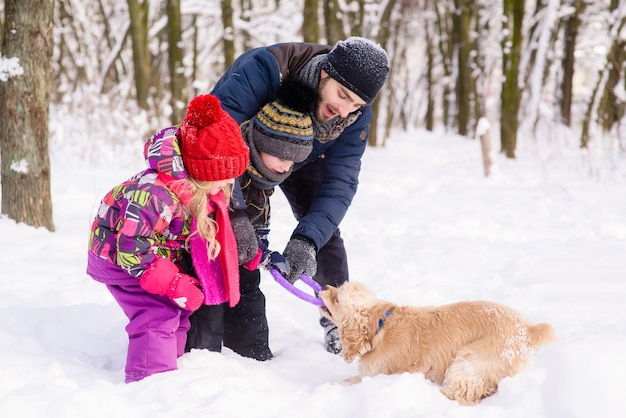 Happy family playing with a dog in snow outdoors