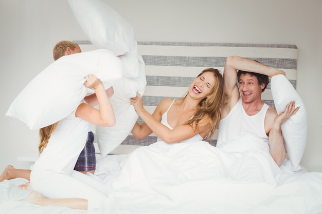 Happy family playing with pillows
