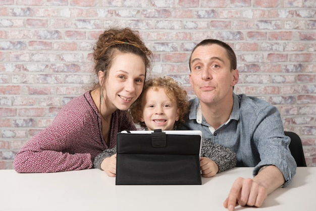 Happy family playing with a tablet computer