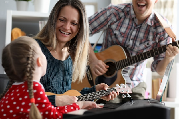 Happy family plays musical instruments