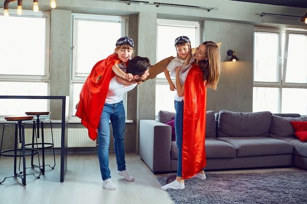 A happy family plays in superheroes indoors.