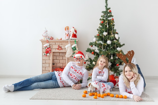 Happy family portrait by christmas tree