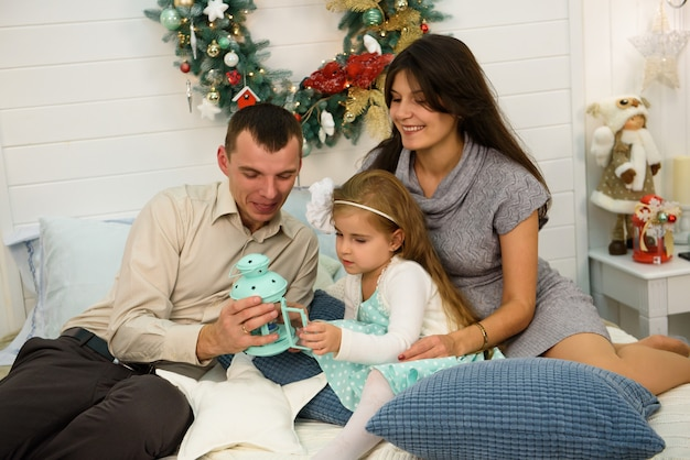 Happy family portrait on christmas, mother, father and child sitting on bed and lighting a candle at home, chritmas decoration around them.