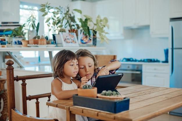 행복한 가족. 현대 아파트 부엌에서 태블릿을 사용하는 형제 자매의 초상화.