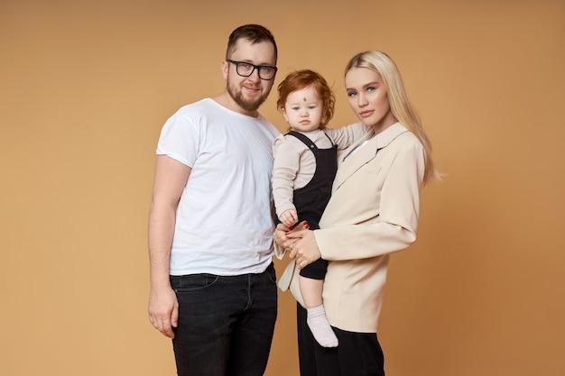幸せな家族。ベージュのママ、パパと娘の肖像画。彼らの小さな娘を腕に抱いて恋に美しいカップル