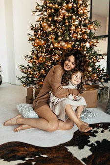 Happy family portrait of pretty mom with daughter dressed knitted sweaters sitting in front of christmas tree and celebrating new year