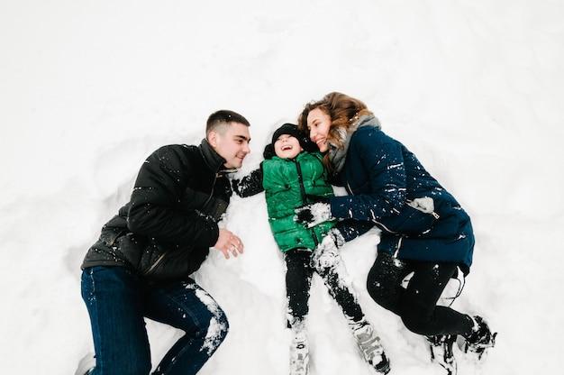 Счастливый семейный портрет прогулки, игры и лежать в снегу в зимнем парке, концепция праздника. эмоции счастья. плоская планировка, вид сверху.