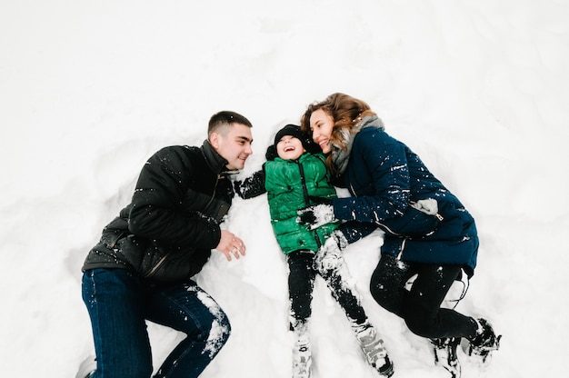 Happy family portrait walking, playing and lie in the snow in winter park, concept of a holiday. emotions of happiness. flat lay, top view.