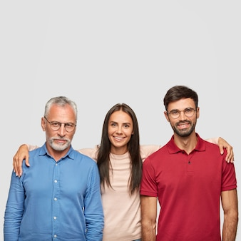 Happy family pose for making common photo: positive senior father, adult daughter and son embrace each other, smile friendly, pose against white wall. people, generation and relations concept