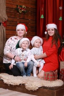 Счастливая семья позирует для фото на рождество. бабушка и мать с двумя детьми в новогодних шапках.