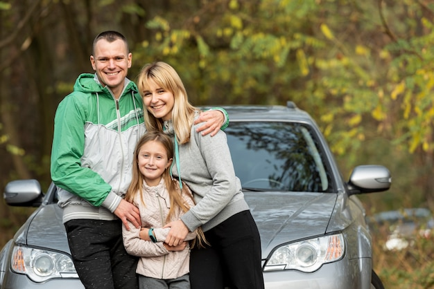 Happy family posing in front of car
