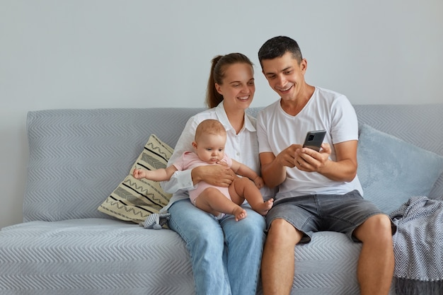 Happy family posing in living room on sofa, mother holding infant daughter, father showing interesting content via mobile phone, smiling people browsing internet together.