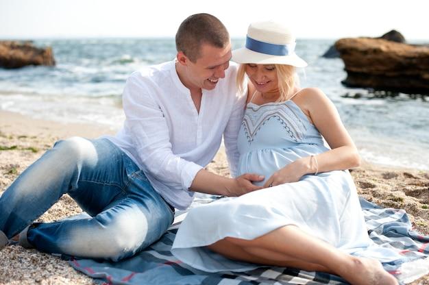 海の近くでポーズをとって幸せな家族、女性は妊娠しています
