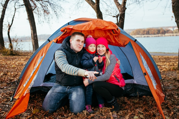 Happy family posing sitting in a tent camping