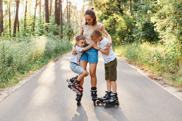 Happy family posing in summer park, mother and two her sons roller skating together, woman spending weekend with her children in active way, hugging kids and smiling happily.