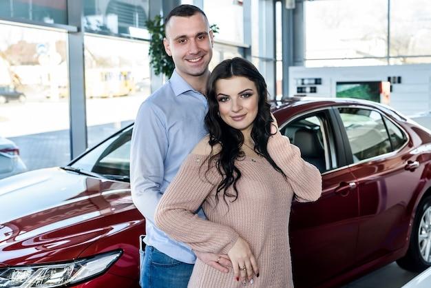 ショールームで車でポーズをとって幸せな家族