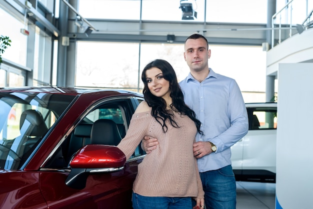 Happy family posing with car in showroom