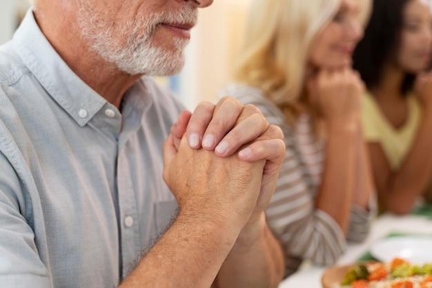 一緒に夕食をとる前に祈る幸せな家族