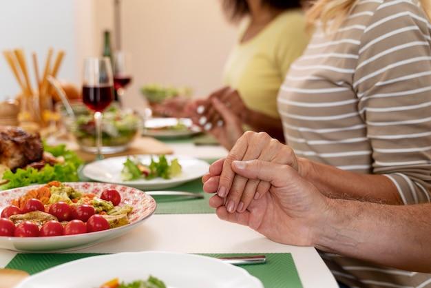 함께 저녁 식사를 하기 전에 기도하는 행복한 가족