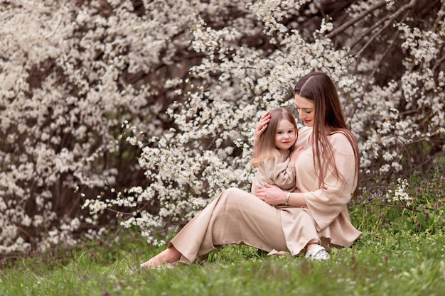 Happy family, pregnant mom with a daughter on a background of flowering trees.
