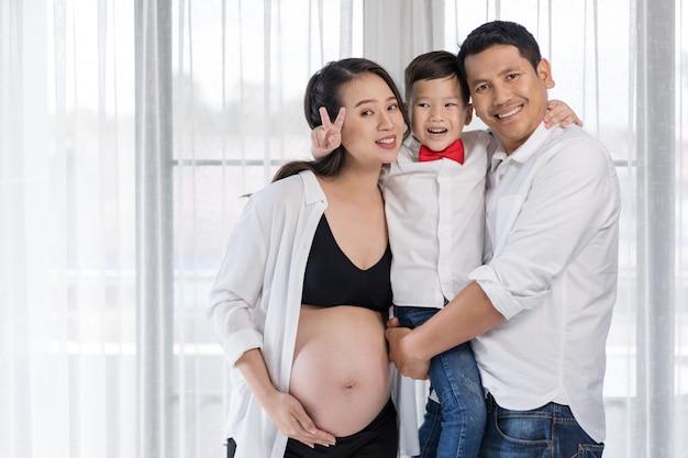 Счастливая семья, беременная мать, отец и сын обнимаются