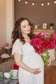 幸せな家族、牡丹の花が付いている台所で妊娠中の女性。母性、妊娠、幸福の概念。花束を持つ少女。牡丹の花束。花と春の少女