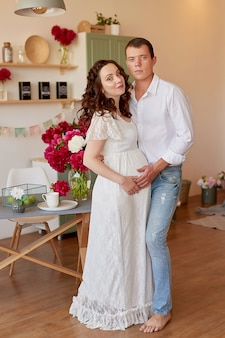 幸せな家族、牡丹の花が付いている台所で小さな娘と妊娠中の女性。親と子の関係。母性、妊娠、幸福の概念。