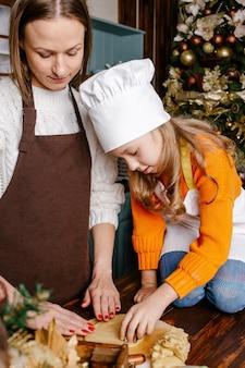 Счастливая семья, приготовление праздничных блюд в домашних условиях. мать и дочь готовят рождественское печенье.