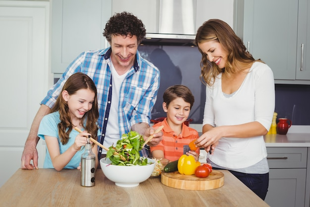 Happy family preparing a vegetable salad