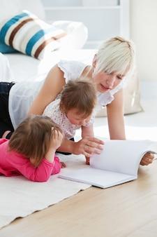Счастливая семья читает книгу на полу