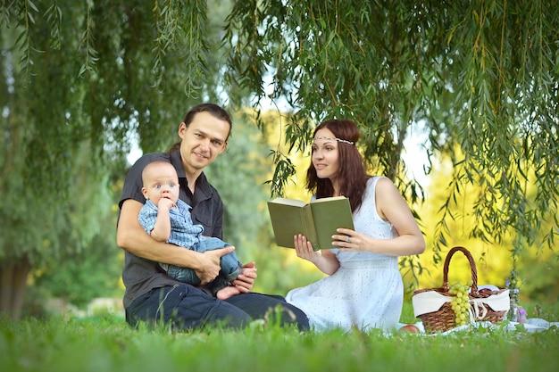공원에서 피크닉에서 어린 아들에게 책을 읽는 행복한 가족