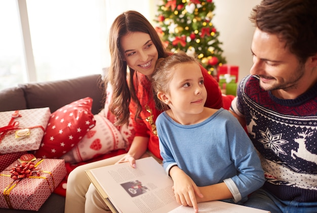 Happy family reading book in christmas