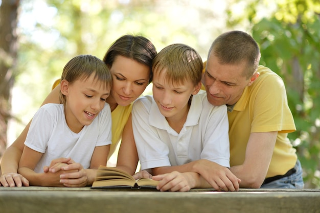 Happy family reading a book outdoors in summer