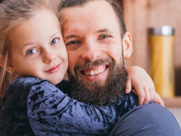 행복한 가족 관계. 사랑과 관심으로 그녀의 사랑하는 아버지를 포옹하는 귀여운 소녀의 근접 촬영 초상화.