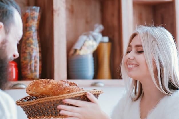 Счастливые семейные отношения. дама приготовила свежий хлеб. пара, наслаждаясь временем вместе на кухне.