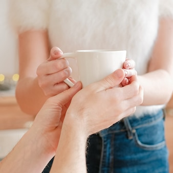 幸せな家族関係。愛、ケア、調和。夫のためにお茶を持っている妻。